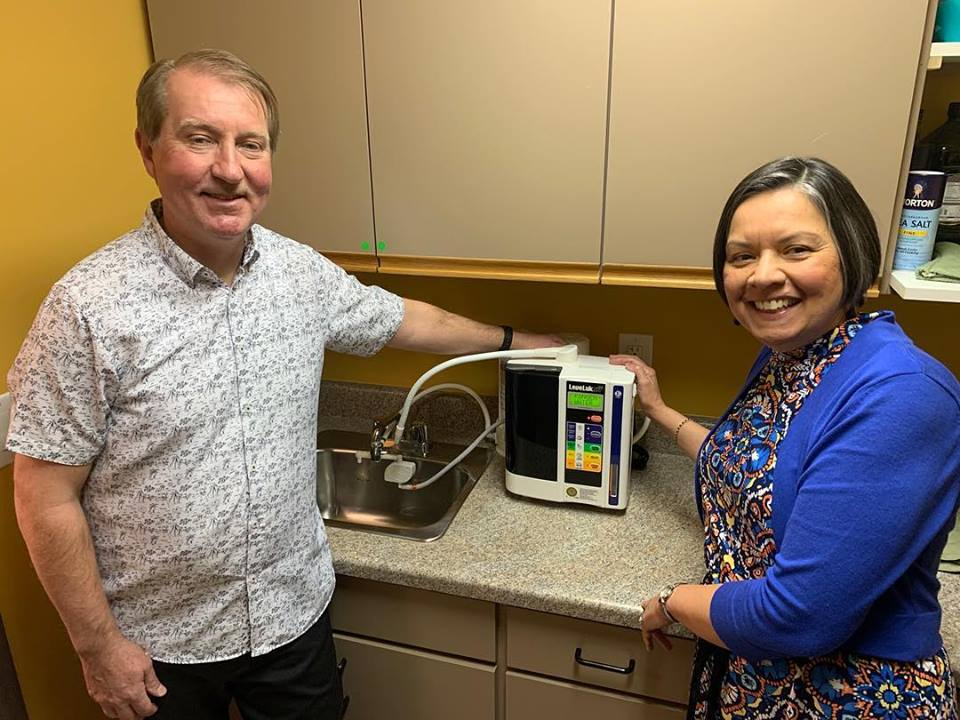 Photo of Doctor Eric and Emma standing next to their new Kangen Water Machine