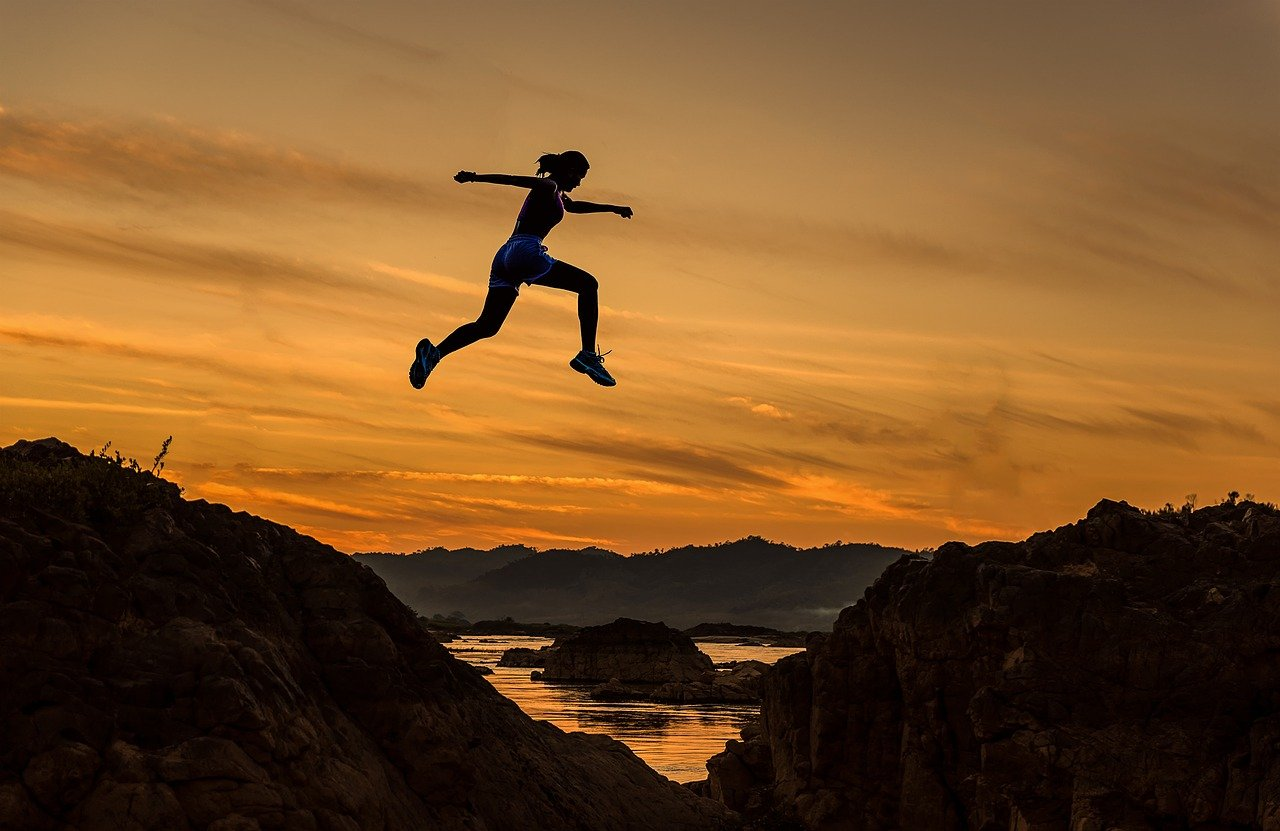 Photo of a woman jumping from one mountain to another