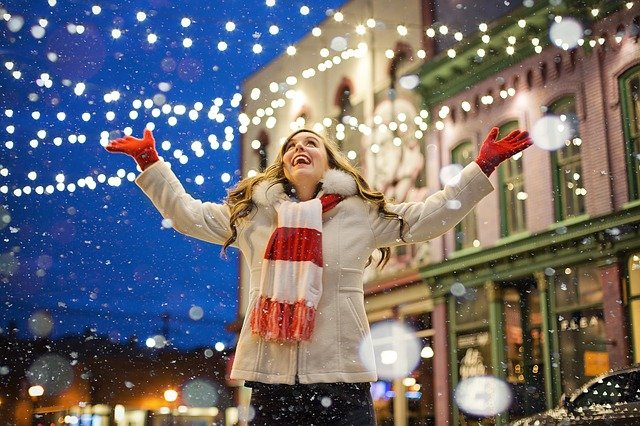 Photo of a young woman wearing a scarf and gloves and enjoying the holiday lights