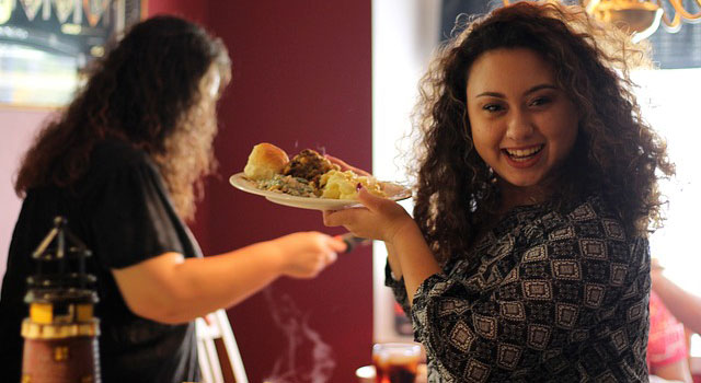 Photo of a happy young woman with a full plate of food